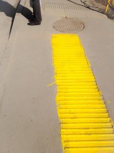 Vorne, längs, gelb: der frisch gestrichene Blindenstreifen an der Ampel. Zum Vergleich hinten quer die alte, staubige Variante.